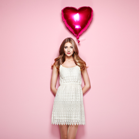Beautiful young woman with heart shape air balloon on color background. Woman on Valentines Day. Symbol of love 版權商用圖片
