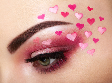 Eye make-up girl with a heart. Valentines day makeup. Beauty fashion. Eyelashes. Cosmetic Eyeshadow. Makeup detail. Creative woman holiday make-up