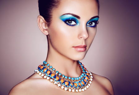 Portrait of young beautiful woman with blue makeup. Face Girl with necklace close up. Fashion jewelry