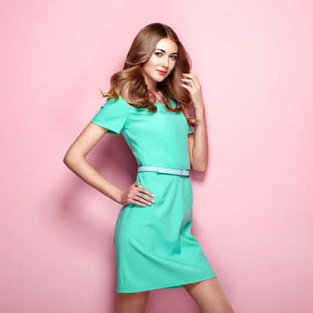 Blonde young woman in elegant green dress. Girl posing on a pink background. Jewelry and hairstyle. Fashion photo