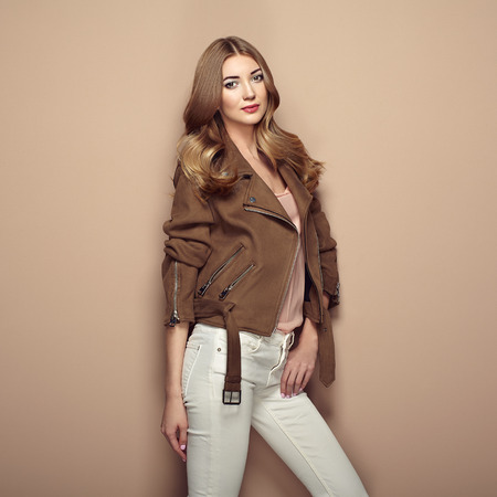 Young blond woman in brown jacket and white jeans. Girl posing on a beige background. Jewelry and hairstyle. Fashion photo Фото со стока