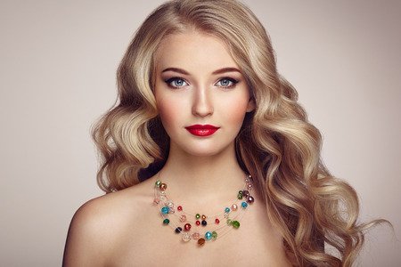Fashion portrait of young beautiful woman with jewelry and elegant hairstyle. Blonde girl with long wavy hair. Perfect make-up.  Beauty style model Imagens - 72490039