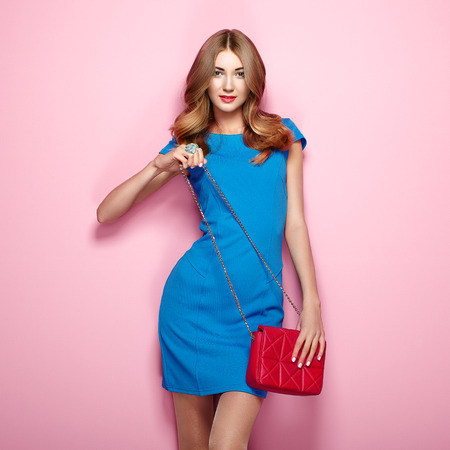 Blonde young woman in elegant blue dress. Girl posing on a pink background. Jewelry and hairstyle. Girl with red handbag. Fashion photo Stok Fotoğraf