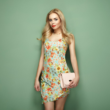 Blonde young woman in floral summer dress. Girl posing on a green background. Jewelry and hairstyle. Girl with handbag. Fashion photo Imagens - 73201637