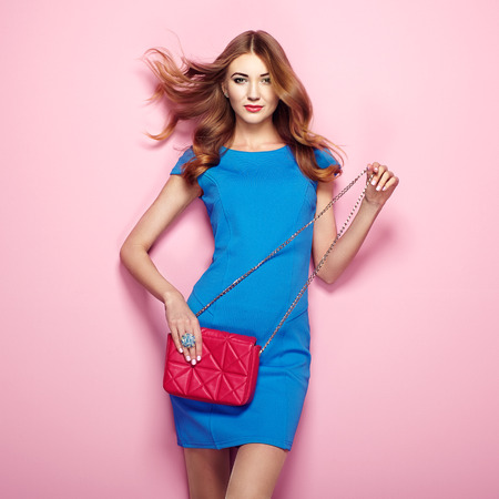 Mujer joven rubia en elegante vestido azul. Presentación de la muchacha en un fondo de color rosa. Joyas y peinado. Chica con bolso rojo. foto de moda
