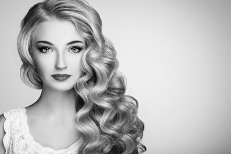Zwart-wit foto van mooie vrouw met elegante kapsel. Blond meisje met lang golvend haar. Perfecte make-up. Schoonheid stijl model