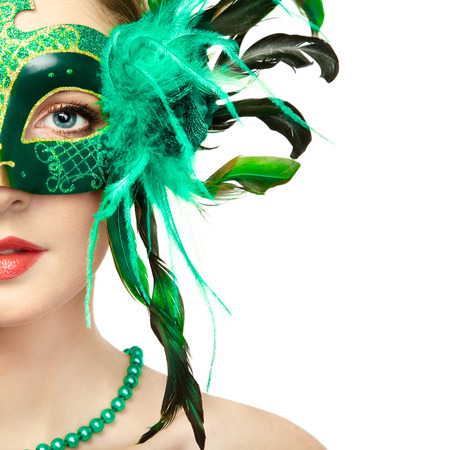 Beautiful young woman in mysterious green Venetian mask. Fashion photo. Holidays and celebrations photo