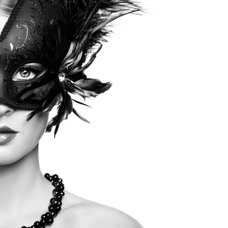 Beautiful young woman in black mysterious venetian mask. Black and White Fashion photo photo