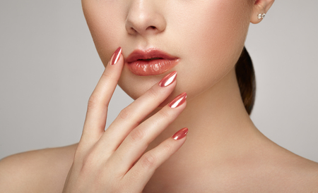 nails: Beauty brunette woman with perfect makeup. Glamour girl. Red lips and nails. Skin care foundation. Beauty girls face isolated on light background. Fashion photo