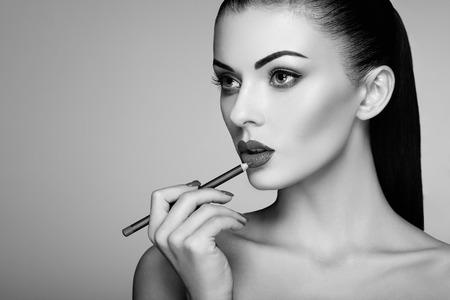 女性絵口紅の黒と白の写真。美しい女性の顔。メイク詳細。完璧な肌を持つ美少女。赤い唇と爪マニキュア