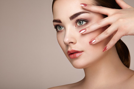 beauty girls: Beauty brunette woman with perfect makeup. Red lips and nails. Perfect eyebrows. Skin care foundation. Beauty girls face isolated on beige background. Fashion photo Stock Photo