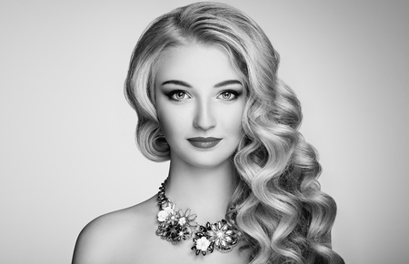 luxurious: Black and white photo of beautiful woman with elegant hairstyle. Blonde girl with long wavy hair. Jewelry and make-up. Beauty style model