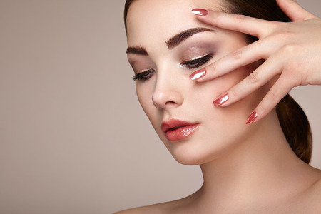 mooie vrouwen: Brunette vrouw met perfecte make-up. Rode lippen en nagels. Perfecte wenkbrauwen. Skin Care Foundation. Beauty meisjes gezicht geïsoleerd op een beige achtergrond. Mode foto Stockfoto