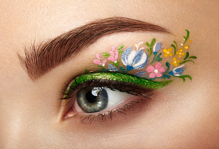 Eye makeup girl with a flowers. Spring makeup. Beauty fashion. Eyelashes. Cosmetic Eyeshadow. Make-up detail. Creative woman holiday make-up 스톡 콘텐츠
