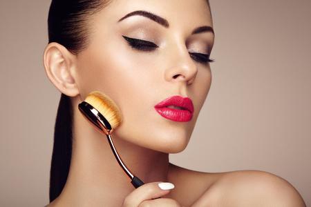 visagist: Makeup artist applies skintone with brush. Beautiful woman face. Perfect makeup. Skincare foundation. Brushes makeup artist
