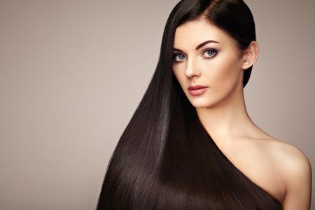 Belle femme avec de longs cheveux lisses. Fille avec le maquillage parfait et coiffure. brune modèle avec des cheveux noirs parfaite santé