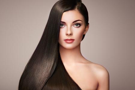 Bella donna con lunghi capelli lisci. Ragazza con perfetta trucco e acconciatura. bruna modello con perfetto capelli scuri sani Archivio Fotografico - 75527870