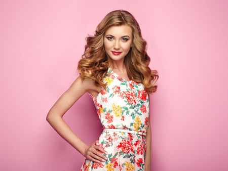 Blonde young woman in floral spring summer dress. Girl posing on a pink background. Summer floral outfit. Stylish wavy hairstyle. Fashion photo. Blonde lady Stockfoto