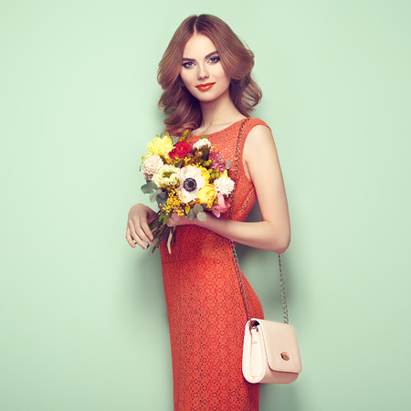 Blonde young woman in elegant red dress. Girl posing on a green background with handbag. Jewelry and hairstyle. Lady with spring bouquet of flowers. Fashion photo