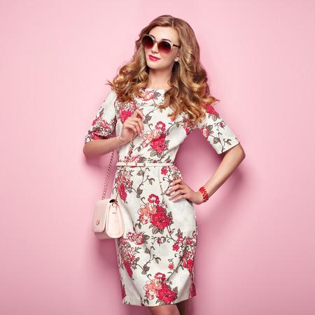 Blonde jonge vrouw in bloemen lente zomerjurk. Meisje poseren op een roze achtergrond. Zomer bloemen outfit. Stijlvol golvend kapsel. Mode foto. Glamour lady in zonnebril met handtas