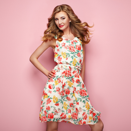 Blonde young woman in floral spring summer dress. Girl posing on a pink background. Summer floral outfit. Stylish wavy hairstyle. Fashion photo. Blonde lady Stok Fotoğraf