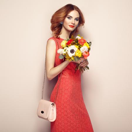 우아한 붉은 드레스에 금발의 젊은 여자. 여자는 핸드백 베이지 색 배경에 포즈. 보석 및 헤어 스타일. 꽃의 스프링 부케와 레이디. 패션 사진