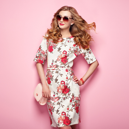 Blonde young woman in floral spring summer dress. Girl posing on a pink background. Summer floral outfit. Stylish wavy hairstyle. Fashion photo. Glamour lady in sunglasses with handbag Stock fotó - 76500420