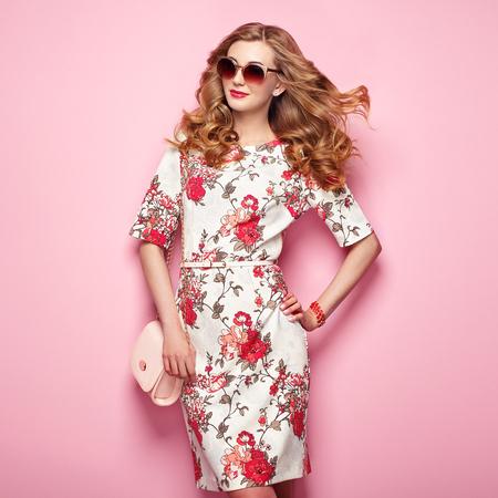 Giovane donna bionda in abito estivo primavera floreale. Ragazza che propone su uno sfondo rosa. Estate vestito floreale. Elegante acconciatura ondulata. Foto di moda. donna glamour in occhiali da sole con la borsa Archivio Fotografico - 76500420