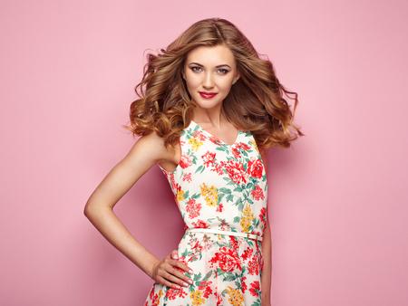 花春夏ドレスで金髪の若い女性。ピンクの背景のポーズの女の子。夏花の服装。スタイリッシュなウェーブのかかった髪型。ファッション写真。ブ