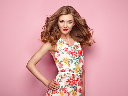Blonde jonge vrouw in bloemen lente zomerjurk. Meisje poseren op een roze achtergrond. Zomer bloemen outfit. Stijlvol golvend kapsel. Mode foto. Blonde dame