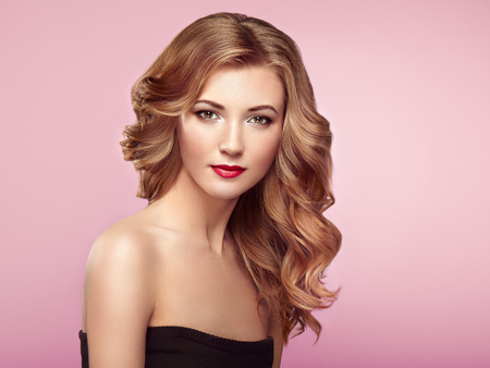 haircut: Blonde woman with long and volume shiny wavy hair . Beautiful model with curly hairstyle. Perfect make-up. Beauty style model