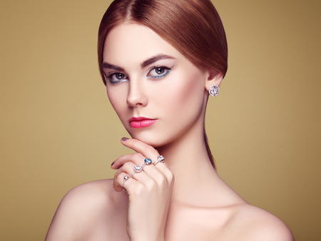 visage: Fashion portrait of young beautiful woman with jewelry. Blonde girl. Perfect make-up and hairstyle.  Beauty style woman with diamond accessories. Silver rings and earrings