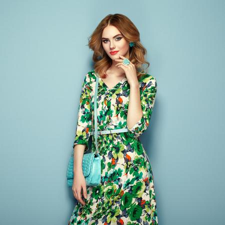 Blond młoda kobieta w sukni kwiatów wiosna. Dziewczyna stwarzających na różowym tle. Lato kwiatów strój. Stylowe fryzury faliste. Fotografia mody. Glamour Dama z torebką Zdjęcie Seryjne