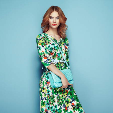 Blonde young woman in floral spring summer dress. Girl posing on a pink background. Summer floral outfit. Stylish wavy hairstyle. Fashion photo. Glamour lady with handbag Imagens - 77028799