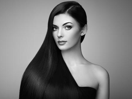 滑らかな長い髪の美しい女性。完璧なメイクと髪型の女の子。完璧な健康な黒い髪とブルネットのモデル。黒と白の写真