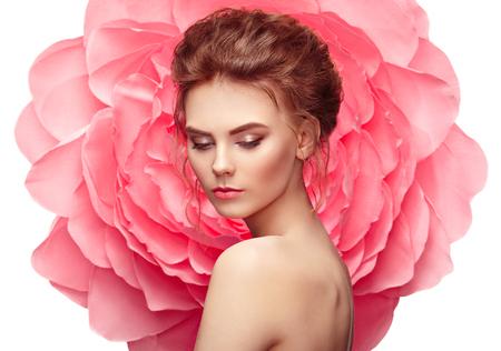 Hermosa mujer en el fondo de una flor grande. Chica de verano belleza modelo con peonía rosa. Mujer joven con elegante peinado y maquillaje. Foto de moda Foto de archivo