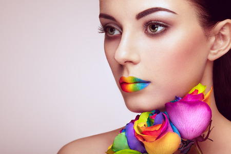 beautiful model: Portrait of beautiful young woman with rainbow rose. Bright colors. Vivid colorful lips. Rainbow make up. Multicolored flowers Stock Photo