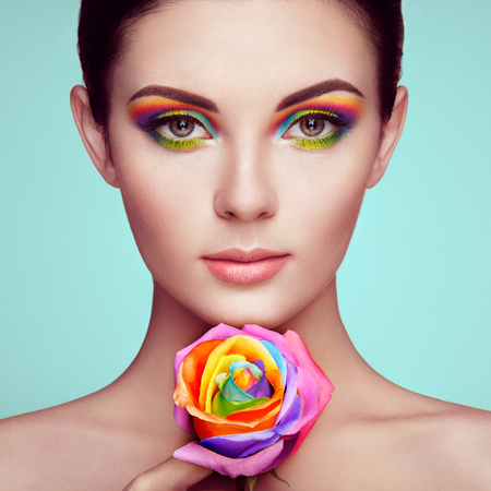 Portrait of beautiful young woman with rainbow rose. Bright colors. Long eyelashes, vivid colorful eyeshadows. Rainbow make up. Multicolored flowers Reklamní fotografie