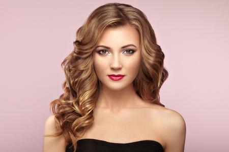 길고 볼륨 반짝이 물결 모양의 머리를 가진 금발의 여자. 곱슬 머리 스타일 아름다운 모델입니다. 완벽한 메이크업. 뷰티 스타일 모델 스톡 콘텐츠