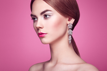 Fashion portrait of young beautiful woman with jewelry. Blonde girl. Perfect make-up and hairstyle.  Beauty style woman with diamond accessories. Pink background