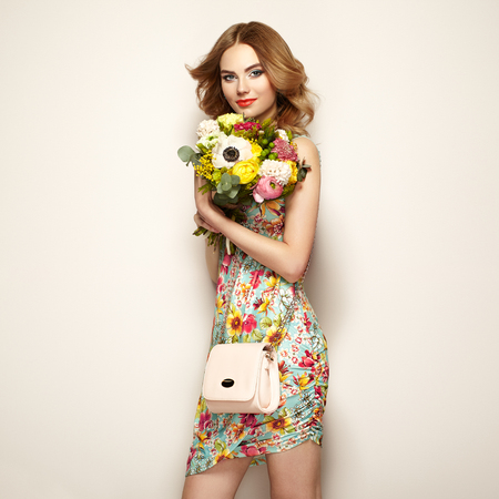 Blonde young woman in elegant floral dress. Girl posing on a beige background with handbag. Jewelry and hairstyle. Lady with spring bouquet of flowers. Fashion photo Фото со стока
