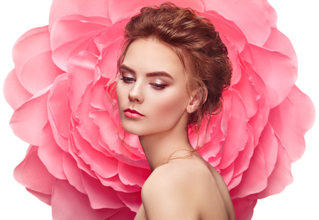 Hermosa mujer en el fondo de una flor grande. Belleza chica modelo de verano con peonía rosa. Mujer joven con peinado elegante y maquillaje. Foto de moda Foto de archivo