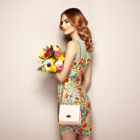 Blonde young woman in elegant floral dress. Girl posing on a beige background with handbag. Jewelry and hairstyle. Lady with spring bouquet of flowers. Fashion photo 版權商用圖片