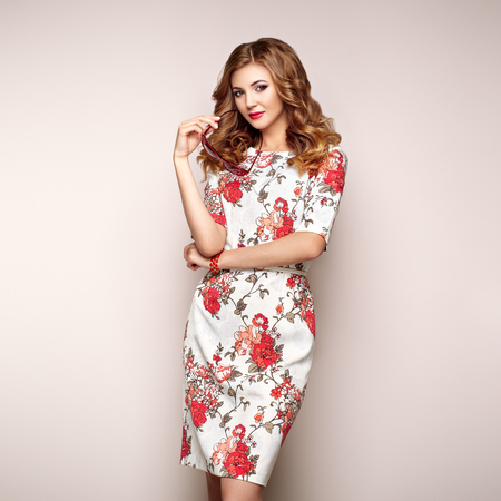 Blonde young woman in floral spring summer dress. Girl posing on a white background. Summer floral outfit. Stylish wavy hairstyle. Fashion photo. Glamour lady with sunglasses Stock Photo