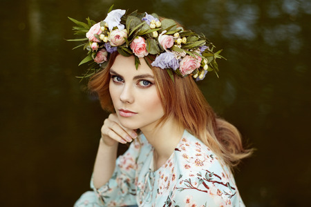 Beautiful blonde woman with flower wreath on her head. Beauty girl with flowers hairstyle. Girl in a summer forest. Fashion photo