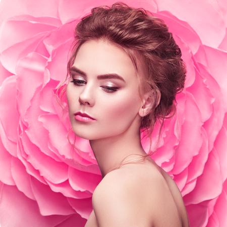 Schöne Frau auf dem Hintergrund einer großen Blume. Schönheit Sommer Modell Mädchen mit rosa Pfingstrose. Junge Frau mit eleganter Frisur und Make-up. Modefoto