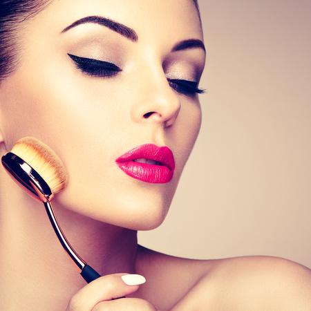 Makeup artist applies skintone with brush. Beautiful woman face. Perfect makeup. Skincare foundation. Brushes makeup artist