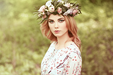 luxurious: Beautiful blonde woman with flower wreath on her head. Beauty girl with flowers hairstyle. Girl in a summer forest. Fashion photo