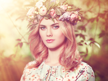 Bella donna bionda con corona di fiori sulla sua testa. Ragazza di bellezza con i fiori acconciatura. Ragazza in una foresta di estate. foto di moda