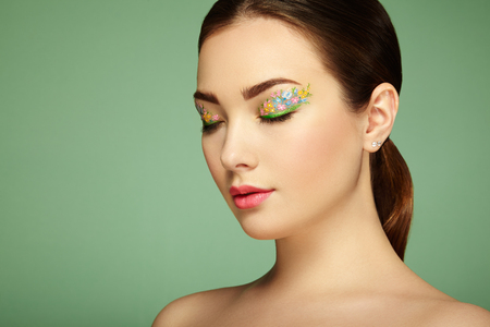 Young beautiful woman with flower makeup eyes. Spring makeup. Beauty fashion. Eyelashes. Cosmetic Eyeshadow. Make-up detail. Girl on green background photo